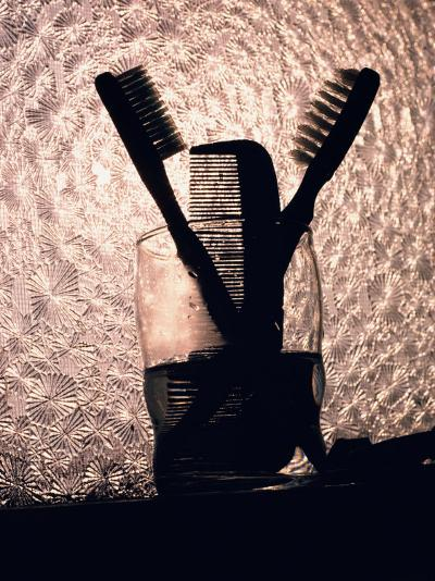 A Comb and Two Toothbrushes on a Bathroom Windowsill-Stephen St^ John-Photographic Print