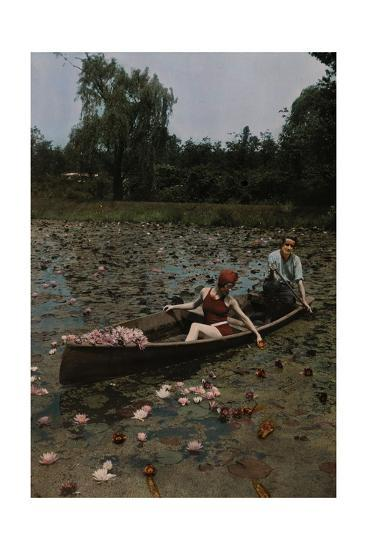 A Couple in a Boat Paddle on a Lily Pond and Collect Flowers-Charles Martin-Photographic Print