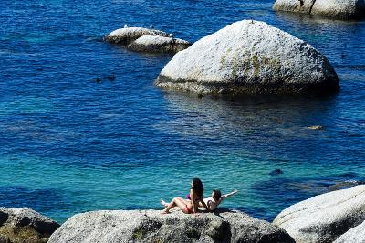 A Couple Sunbathing on a Boulder Above a Clear Blue Sea-Jason Edwards-Photographic Print