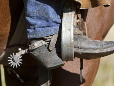 A Cowboy Boot and Spur in a Stirrup of a Saddle-Robbie George-Photographic Print