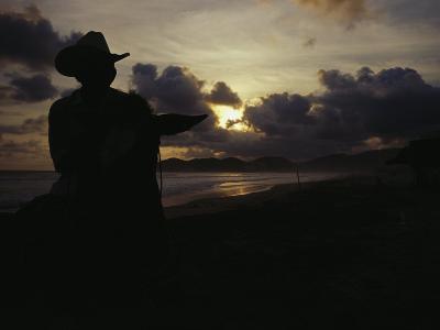 A Cowboy on His Horse Enjoys Sunrise on a Beach-Raul Touzon-Photographic Print