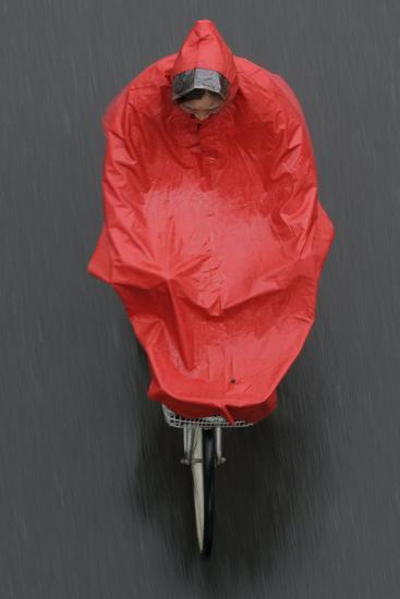 A Cyclist Rides in the Rain on a Street in Beijing-Michael Reynolds-Photographic Print