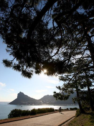 A Cyclist Rides Past the Sentinel Peak in Hout Bay Near Cape Town, South Africa-Jon Hrusa-Photographic Print