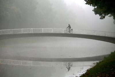 A Cyclists Rides His Bike over a Bridge at the Karlsaue Park in Kassel, Germany-Uwe Zucchi-Photographic Print