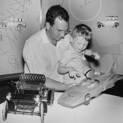 A Father Shows His Son Two Model Cars from General Motors--Photographic Print