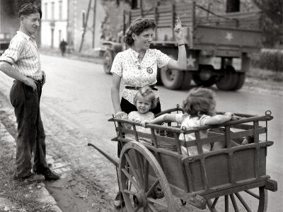 A French Couple with Two Young Girls in a Carriage Is Watching a Convoy of GMC Passing--Photographic Print