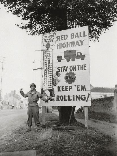 """A Gi Standing Next to a Sign Saying """"Red Ball Highway""""--Photographic Print"""