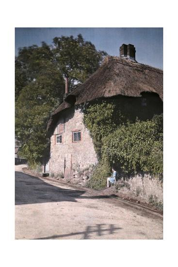 A Girl Sits on a Wall Next to an Old Thatched Cottage-Clifton R^ Adams-Photographic Print
