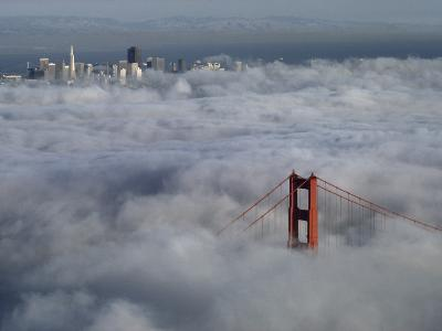 A Glowing Tower of the Golden Gate Bridge Rises Above the Fog-Jim Sugar-Photographic Print