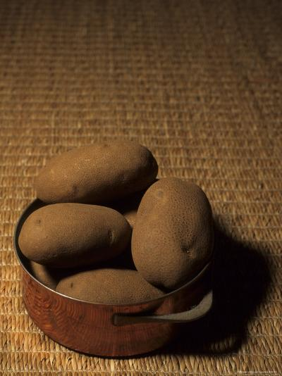 A Group of Baking Potatoes Sit in a Brass Cooking Pot-Taylor S^ Kennedy-Photographic Print