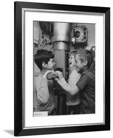A Group of Boys Take Turns Looking Through a Periscope Interactive--Framed Photographic Print
