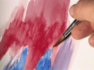 A Hand Painting an Abstract Picture with a Brush