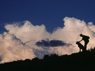 A Hiker and Her Dog Below Thunderheads in Arid Volcanic Tablelands-Gordon Wiltsie-Photographic Print