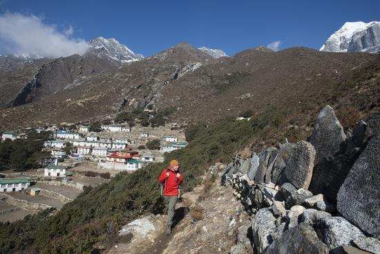 A Hiker Walks Past a Wall of Mani Stones Inscribed with an Ancient Tibetan Mantra-Alex Treadway-Photographic Print