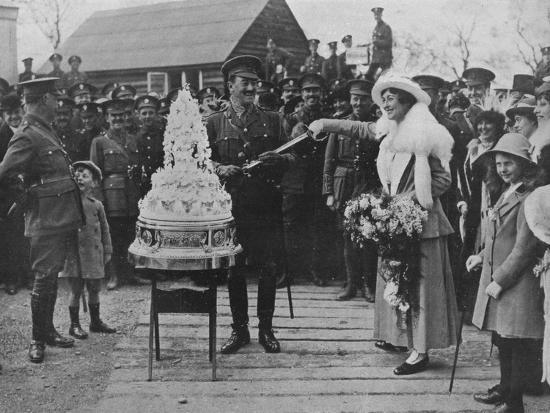 'A khaki wedding: Cutting the wedding cake with the bridegroom's sword', 1915-Unknown-Photographic Print