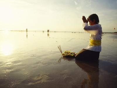 A Kneeling Hindu Balinese Woman Prays and Gives Offerings at Sunset--Photographic Print