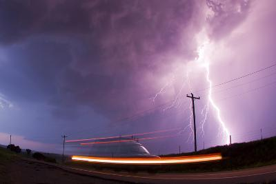 A Large Lightning Bolt Strikes Behind a Storm Chaser's Moving Van-Mike Theiss-Photographic Print