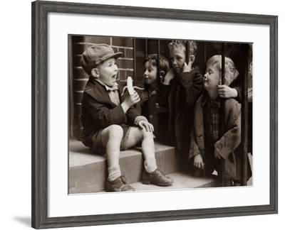 A Little Boy Holding a Banana Whilst Other Children Gaze Longingly at It--Framed Photographic Print