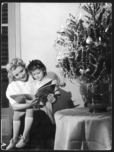 A Little Girl Sits on Her Mother's Knee and Reads a Book Beside the Christmas Tree--Photographic Print