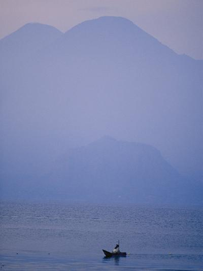 A Lone Boat Plies a Mountain Lake in Early Morning Fog-Raul Touzon-Photographic Print
