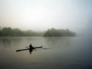 A Lone Rower Slowly Maneuvers His Craft Down the Schuykill River Through a Thick Fog