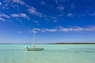 A Lone Sailboat Anchored in Turquoise Water-Mike Theiss-Photographic Print