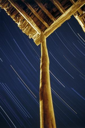 A Long Exposure of Sky Motion Shows Star Trails over the Wooden Roof of a Village House-Babak Tafreshi-Photographic Print