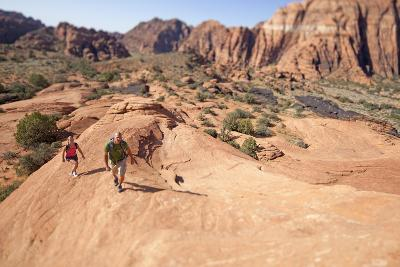 A Man and Woman Hiking in Snow Canyon State Park, Utah-John Burcham-Photographic Print