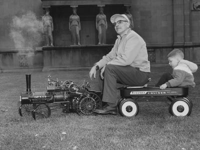 A Man and Young Boy Ride in a Wagon Being Pulled by a Model 'Case' Locomotive--Photographic Print
