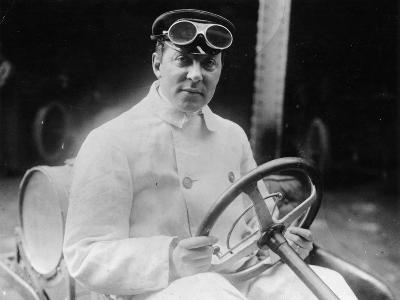 A Man at the Wheel of His Car Dressed in a Driving Coat and Goggles--Photographic Print