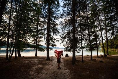 A Man Carrying A Canoe At Priest Lake In North Idaho-Ben Herndon-Photographic Print
