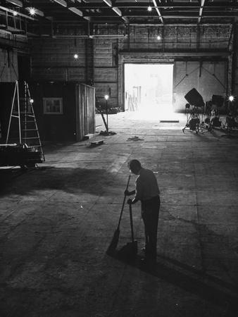 A Man Cleaning Up the Empty Sound Stage--Photographic Print