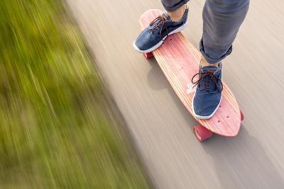 A Man Cruising Along On His Skateboard-Axel Brunst-Photographic Print