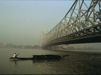 A Man Guides a Boat under a Bridge on the Hooghly River at Calcutta-Ed George-Photographic Print