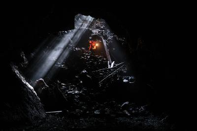 A Man Holding A Propane Lantern Exits The Cheese Cave, A 2,000 Foot Lava Tube-Ben Herndon-Photographic Print