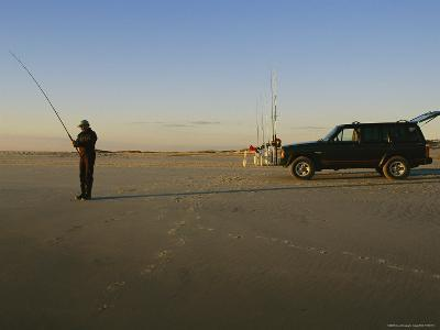 A Man Holds a Fishing Pole While Standing Near His Jeep Truck-Stephen Alvarez-Photographic Print