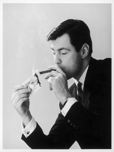 A Man in a Suit Lights His Cigar with a One Pound Note