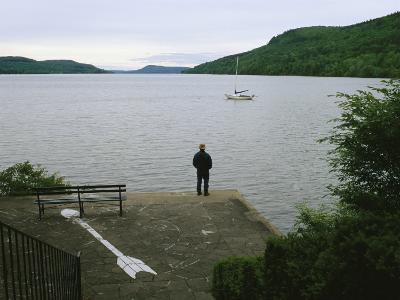 A Man Looks out at a Sailboat Anchored on Otsego Lake-Raymond Gehman-Photographic Print