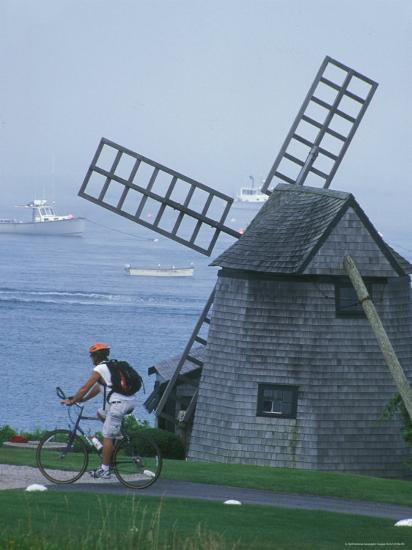 A Man on a Bicycle Passing a Windmill on the Shore in Cape Cod-Darlyne A^ Murawski-Photographic Print