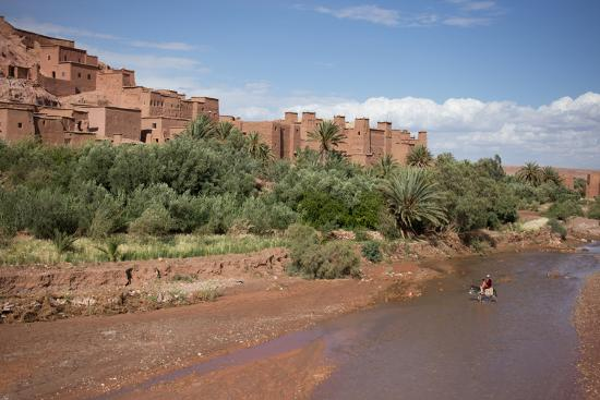 A Man on a Donkey Crossing the River in Front of Ait Benhaddou, Morocco-Erika Skogg-Photographic Print