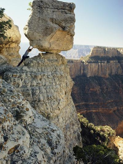 A Man Pretends to Push a Huge Boulder into the Canyon-W^ E^ Garrett-Photographic Print