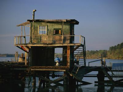 A Man Sits on a Pier Near a Dilapidated Shack-Raymond Gehman-Photographic Print