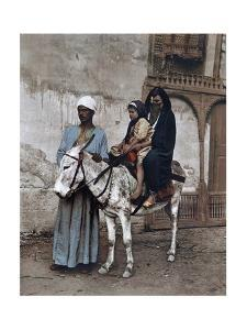 A Man Stands with a Veiled Woman and Child Sitting on a Donkey