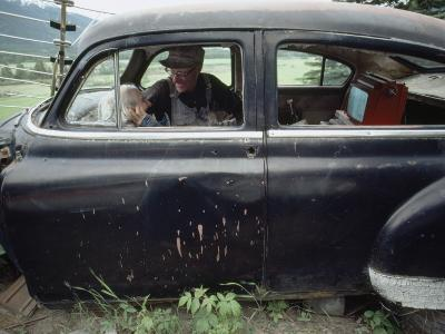 A Mother and Son Watch Television in an Old Car-Chris Johns-Photographic Print