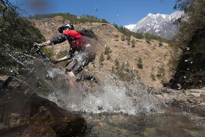 A Mountain Biker Blasts Through a Stream in the Mountains of Nepal-Alex Treadway-Photographic Print