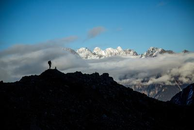 A Mountaineer Stands on a Mountaintop with Higher Peaks Visible in the Sunlight Beyond-Cory Richards-Photographic Print
