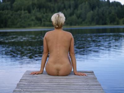 A Naked Woman Sitting on a Dock by a Lake--Photographic Print