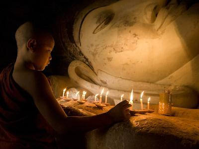 A Novice Monk Lighting Candles at a Massive Buddha Statue in Burma (Myanmar)-Kyle Hammons-Photographic Print