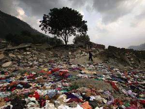 A Pakistani Refugee Walks Past Clothing Left Strewn on the Ground