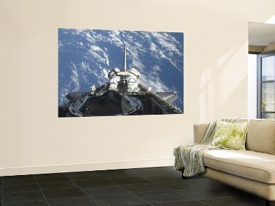 A Partial View of Space Shuttle Atlantis Backdropped by a Blue and White Earth--Wall Mural